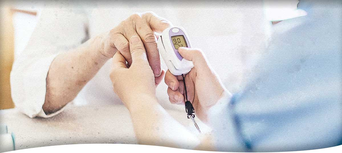 A nurse helping a client use a fingertip pulse oximeter to measure her blood oxygen level
