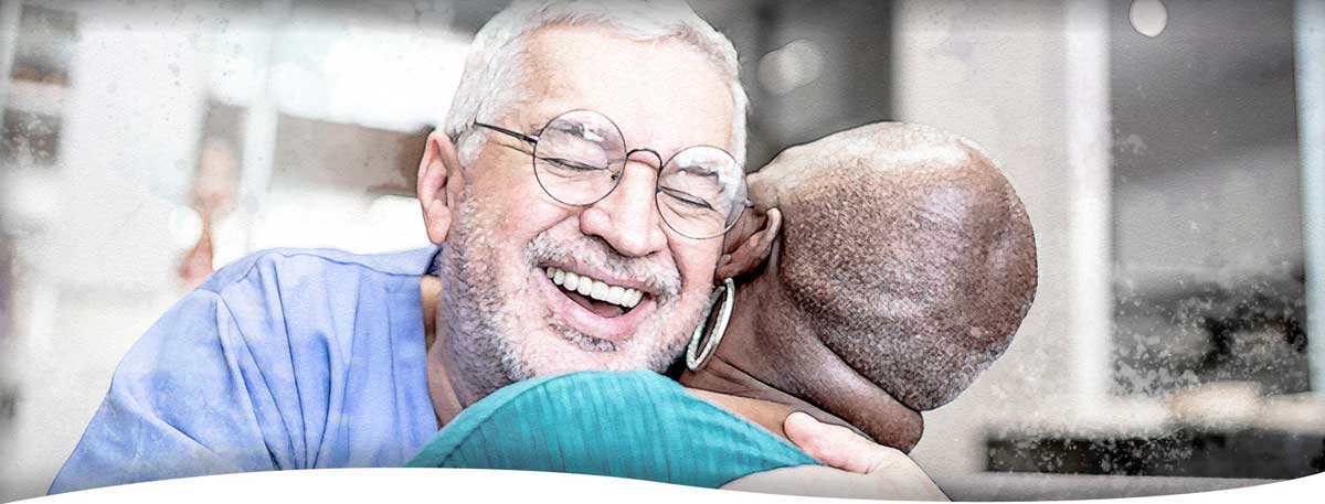 Home healthcare nurse and client joyfully hugging each other