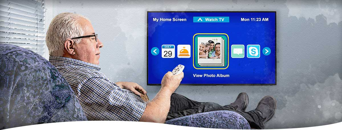 A man sitting in a recliner using his remote to view photo albums on his e-Fox Telehealth TV system