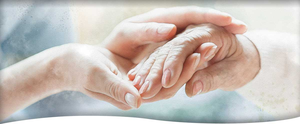 A woman caregiver gently holding the hand of a senior-aged woman