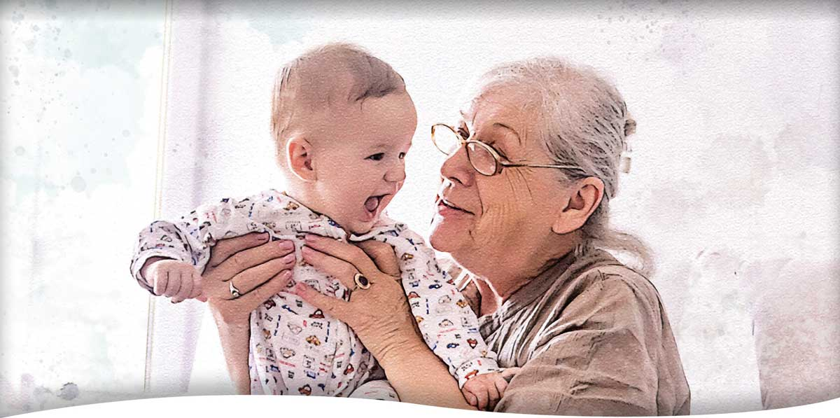A small baby expresses joy as his grandmother lovingly picks him up