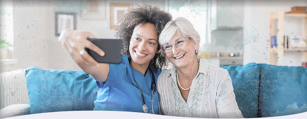 A home healthcare nurse and her client smile as the nurse holds a cell phone to take a selfie of them together in the client's home